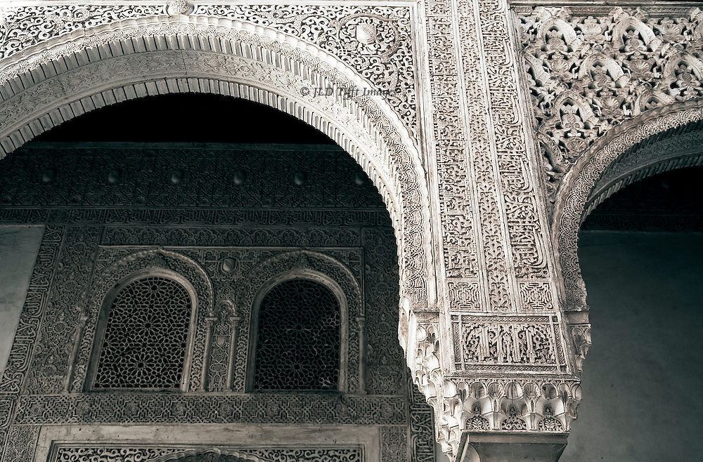 Detail of an arcade in the Patio de Arrayanes, in the Alhambra, showing the richness and delicacy of its all-over ornament: Arabic inscriptions, rinceaux, foliate, geometric, and rudimentary stalagtite ornament.
