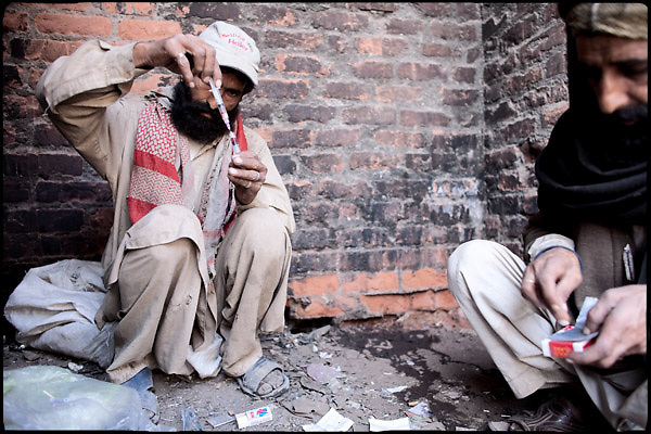"Two men are preparing their dose of heroin to consume it. Morgh Mandi, Rawalpindi, Pakistan, on friday, November 28 2008.....""Pakistan is one of the countries hardest hits by the narcotics abuse into the world, during the last years it is facing a dramatic crisis as it regards the heroin consumption. The Unodc (United Nations Office on Drugs and Crime) has reported a conspicuous decline in heroin production in Southeast Asia, while damage to a big expansion in Southwest Asia. Pakistan falls under the Golden Crescent, which is one of the two major illicit opium producing centres in Asia, situated in the mountain area at the borderline between Iran, Afghanistan and Pakistan itself. .During the last 20 years drug trafficking is flourishing in the Country. It is the key transit point for Afghan drugs, including heroin, opium, morphine, and hashish, bound for Western countries, the Arab states of the Persian Gulf and Africa..Hashish and heroin seem to be the preferred drugs prevalence among males in the age bracket of 15-45 years, women comprise only 3%. More then 5% of whole country's population (constituted by around 170 milion individuals),  are regular heroin users, this abuse is conspicuous as more of an urban phenomenon. The substance is usually smoked or the smoke is inhaled, while small number of injection cases have begun to emerge in some few areas..Statistics say, drug addicts have six years of education. Heroin has been identified as the drug predominantly responsible for creating unrest in the society."""
