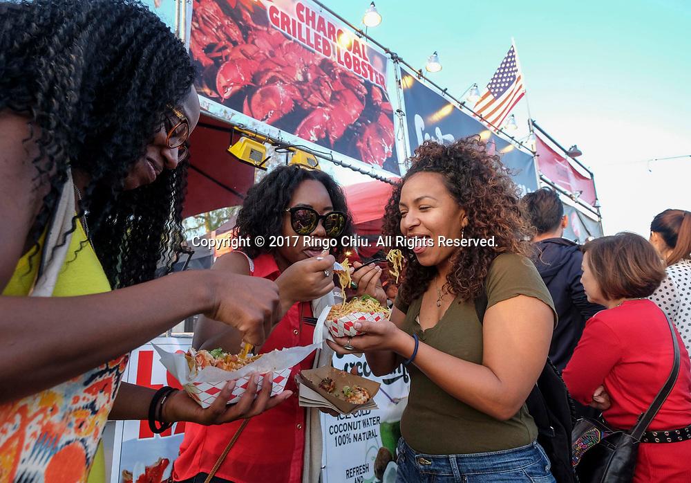 6月30日,民众在626夜市享用美食。当天 ,在美国洛杉矶阿卡迪亚市的圣安娜公园举行626夜市。上百个美食摊位、汇集了洛杉矶周围几乎所有的华人小吃,吸引大批民众参与。新华社发 (赵汉荣摄)<br /> People enjoy the food in front of the food stalls before nightfall at the '626 Night Market' on June 30, 2017 in Arcadia, Caliifronia, the United States. 626 Night Market IS an event that attracts all generations of the Chinese American community and showcases many San Gabriel Valley food vendors. (Xinhua/Zhao Hanrong)(Photo by Ringo Chiu)<br /> <br /> Usage Notes: This content is intended for editorial use only. For other uses, additional clearances may be required.