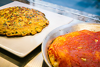 NAPLES, ITALY - 4 JANUARY 2019: A zucchini frittata and marinara pizza are seen here at the street food counter of Janarius, a restaurant in Naples, Italy, on January 4th 2019.<br /> <br /> Janarius is a typical Neapolitan gourmet restaurant and shop founded by Francesco Andoli in September 2018 in via Duomo, in front of the Naples's Duomo and treasure of Saint Janarius. Saint Janarius is the patron saint of Naples.