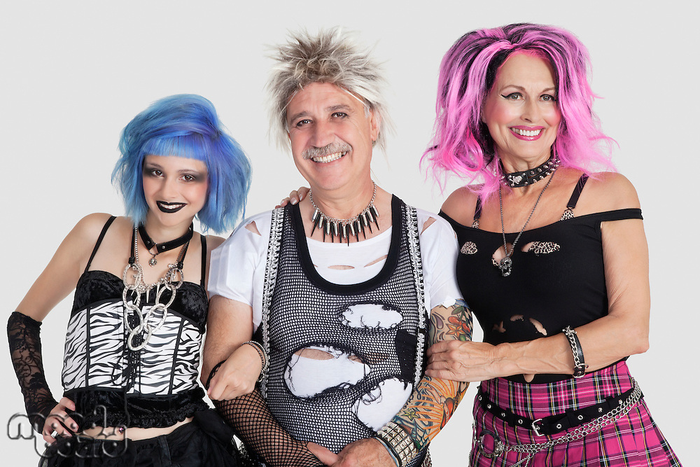 Portrait of senior man with punk females over gray background
