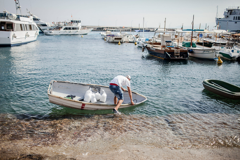 "04 August 2017, Capri Italy - A fisherman get on board of her small boat at the port of ""Marina Grande""."
