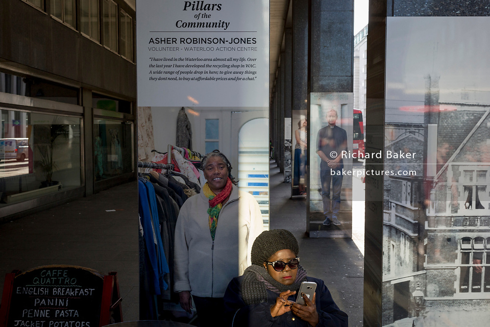 A lady checks her messages in front of a community poster featuring a local welfare centre in Waterloo, on 21st February 2019, in London, England.