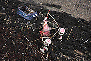 Flotsam rubbish and waste washed up on the sandy foreshore of the River Thames in Grays, Essex England.