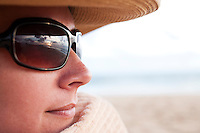 Woman in black sunglasses and a beach hat enjoying the sunset at the beach. Natural woman with very little touch up to face.