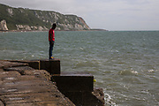 An unaccompanied minor refugee child stands alone on the coast line in Kent. United Kingdom.  (photo by Andrew Aitchison / In pictures via Getty Images)