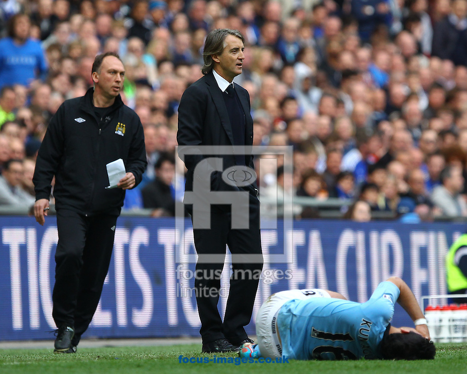 Picture by John Rainford/Focus Images Ltd +44 7506 538356.14/04/2013.Sergio Aguero of Manchester City lays injured as Roberto Mancini and David Platt look on during the FA Cup semi final match at Wembley Stadium, London.