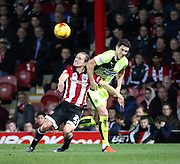 Brentford striker Lasse Vibe battling for the ball with Huddersfield Town defender and captain Mark Hudson during the Sky Bet Championship match between Brentford and Huddersfield Town at Griffin Park, London, England on 19 December 2015. Photo by Matthew Redman.