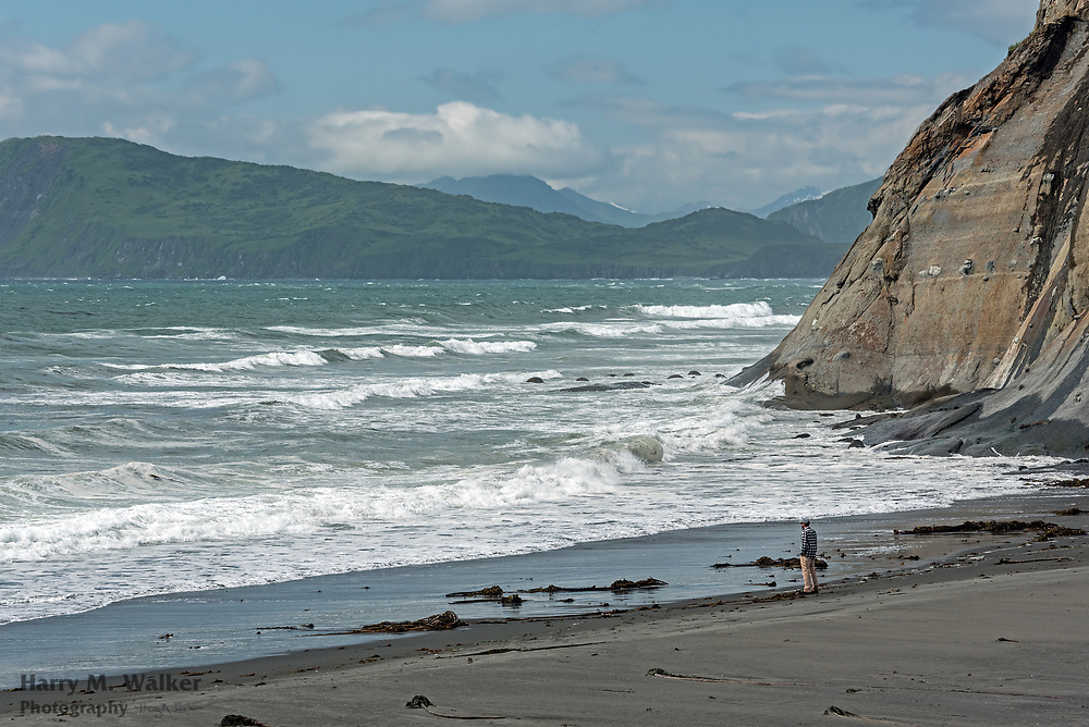 Wind driven Pacific Ocean waves at Fossil Beach with man looking at surf; Narrow Cape; Kodiak Island Alaska
