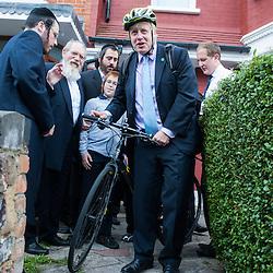 London, UK - 7 August 2014: The Mayor Boris Johnson leaves with his bike after meeting Rabbi Oscher Schapiro and the Orthodox Jewish community in Stamford Hill, London