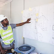 CAPTION: Tsungai reviews the plans for the Kufandada River Protection and Irrigation Scheme Project. Construction is now complete, and the project will soon be officially handed over to its beneficiaries. LOCATION: Near Bikita Rural Hospital, Bikita District, Masvingo Province, Zimbabwe. INDIVIDUAL(S) PHOTOGRAPHED: Tsungai Mavambe.