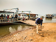 11 MARCH 2016 - LUANG PRABANG, LAOS: A crewman ties a ferry ferry to the riverbank after it crossed the Mekong River near Luang Prabang. Laos is one of the poorest countries in Southeast Asia. Tourism and hydroelectric dams along the rivers that run through the country are driving the legal economy.       PHOTO BY JACK KURTZ