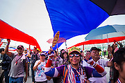 "09 MAY 2014 - BANGKOK, THAILAND: Thai anti-government protestors carry a huge Thai flag through the streets near Government House in Bangkok. Thousands of Thai anti-government protestors took to the streets of Bangkok Friday to start their ""final push"" to bring the popularly elected of government of Yingluck Shinawatra. Yingluck has already been forced out by a recent court ruling that forced her to resign and she is facing indictment by the National Anti Corruption Commission of Thailand for alleged improprieties related to a government rice price support scheme. The protestors Friday were marching to demand that she not be allowed to return to politics. The courts have not banned her party, Pheu Thai, which has formed an interim caretaker government to govern until elections expected in July, 2014. Suthep Thaugsuban, secretary-general of the People's Democratic Reform Committee (PDRC),  said the president of the Supreme Court and the new senate speaker, who would be selected Friday, should set up an ""interim people's government and legislative assembly."" He went onto say that if they didn't, he would.     PHOTO BY JACK KURTZ"