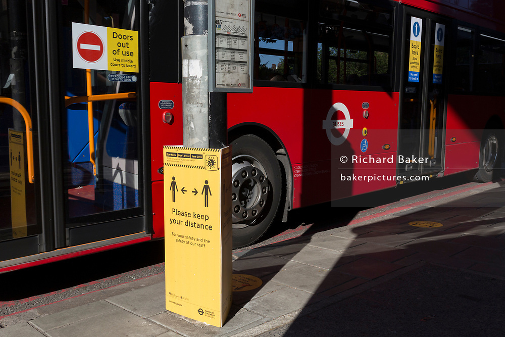 As the number of new Coronavirus cases in the UK climbs to 201,101, with UK deaths now standing at 30,076 - the highest recorded in Europe, a Transport For London (TFL) sign asks the public to maintain safe social distances while travelling on the capital's public transport such as buses during the continuing Covid lockdown, on 6th May 2020, in south London, England. Front doors on London buses are now disabled to avoid exposure of drivers to the virus, plus no fares are being taken on journeys to further avoid card reader contact.