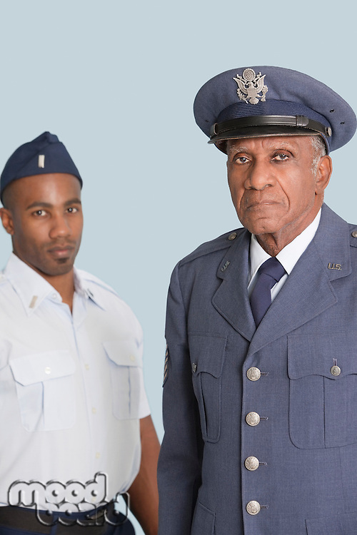 Portrait of senior US Air Force officer with male cadet over light blue background