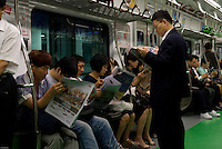 Morning commuters reading newspapers in Seoul subway, South Korea.