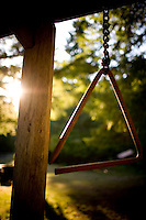 A triangle is used for the call to meals at camp at Opal Creek, Oregon.  Sunset on a green and amber summer evening camping.