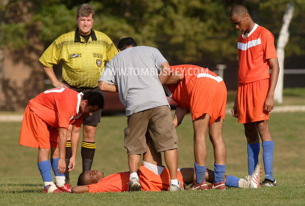 Middletown, N.Y. - Teammates gather around a Hostos Community College player who is lying on the ground because of a leg cramp during a men's soccer game against Orange County Community College played on a warm afternoon on Oct. 6, 2007.
