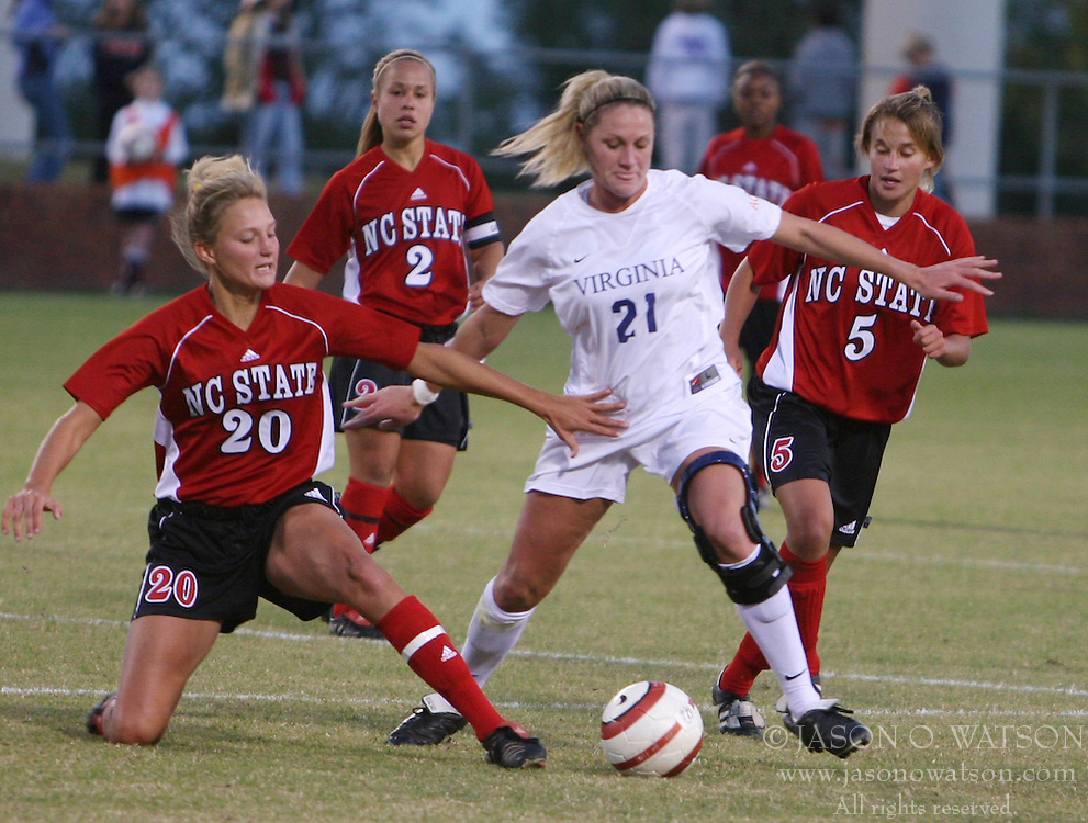 UVA fourth-year Kelly Hammond (#21) fights off NC State defenders while protecting the ball.  Hammond assisted on UVA's second goal en route to a 2-0 victory.