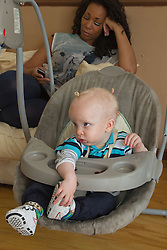 Small boy in rocker with mother in background. (This photo has extra clearance covering Homelessness, Mental Health Issues, Bullying, Education and Exclusion, as well as the usual clearance for Fostering & Adoption and general Social Services contexts,)