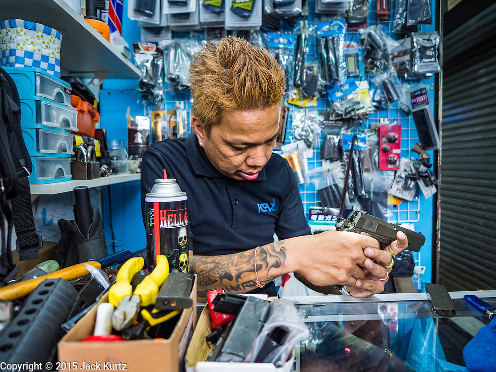 11 OCTOBER 2015 - BANGKOK, THAILAND: A man who repairs replica guns works on a pistol in his shop in Saphan Lek on what Bangkok city officials is saying was the last full day of business in the market. Many shops in the market are already closed. Street vendors and illegal market vendors in the Saphan Lek area will be removed in the next two weeks as a part of an urban renewal project coordinated by the Bangkok Metropolitan Administration. About 500 vendors along Damrongsathit Bridge, popularly known as Saphan Lek, have until Monday, October 11,  to relocate. Vendors who don't move will be evicted. Saphan Lek is one of several markets and street vending areas being closed in Bangkok this year. The market is known for toy and replica guns, bootleg and pirated DVDs and CDs and electronic toys.    PHOTO BY JACK KURTZ