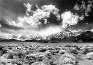 An early spring storm pushes against the snow-capped eastern Sierras from the west as seen from Highway 395 near Lone Pine.