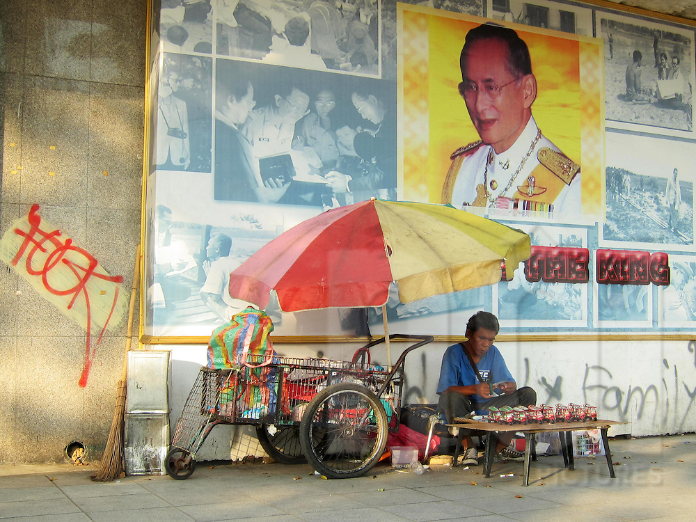 A Thai man builds tuk-tuk models in front of a wall displaying portraits of the royal family, Thailand, Southeast Asia