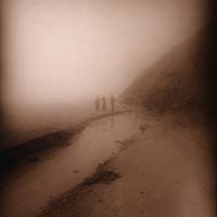 trio of figures in isolation on rainy beach