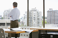 Business man looking out of office window back view
