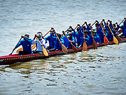 29 OCTOBER 2018 - PHRA PRADAENG, SAMUT PRAKAN, THAILAND: A long boat racing team paddles their boat up river towards the starting line before the long boat races in Phra Pradaeng. The longboat races go about one kilometer down the Chao Phraya River to the main pier in Phra Pradaeng. The boats are crewed by about 20 oarsmen. Longboat racing traditionally marks the end of the Buddhist Rains Retreat (called Buddhist Lent) in Thai riverside communities.        PHOTO BY JACK KURTZ