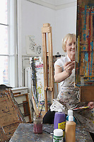 Mature female artist painting at easel in art studio