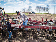 "20 APRIL 2020 - BOUTON, IOWA: A farmer and his son work on his tiller in a field near Bouton. Iowa farmers are prepping their fields for the 2020 season. The relatively mild winter and dry spring has allowed farmers to get into their fields 1 - 2 weeks earlier than last year. Farmers and agricultural workers are considered ""essential"" workers in Iowa and not subjected to the coronavirus restrictions nonessential workers are. Farmers usually work by themselves, and social distancing guidelines have not impacted them as much as it has workers in Iowa's cities.   PHOTO BY JACK KURTZ"