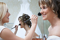 Young woman applying make-up to bride's face