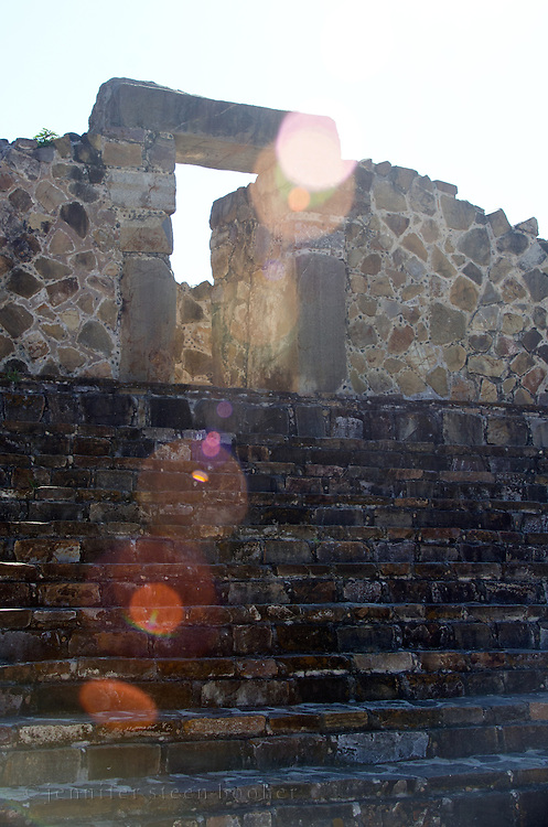 Morning sunlight flares around a doorway into the roofless Palacio complex at Monte Alban, Oaxaca, Mexico.
