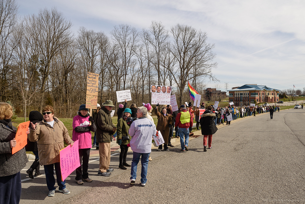 Protest organizers stretch their line from the corner at Tucker Station Road along Plantside Drive closer to where Vice President Pence is speaking. Groups protest The Republican Party's proposed changes to the Affordable Care Act during a visit by Vice President Mike Pence with Kentucky Governor Matt Bevin and business leaders Saturday, March 11, 2017 at Trane Parts and Distribution Center, 12850 Plantside Drive, Louisville, Ky. (Photo by Brian Bohannon)