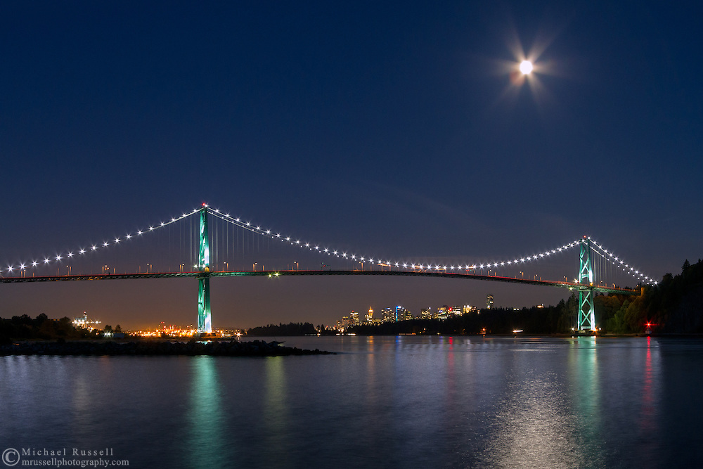 The Moon rises over downtown Vancouver and the Lions Gate Bridge -  from Ambleside Beach Park in North Vancouver, British Columbia, Canada