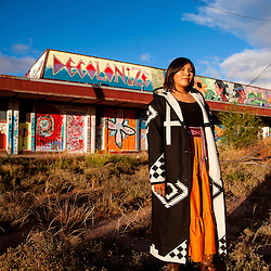 Kayla Begay stands in front of a mural she helped create Navajo, N.M.