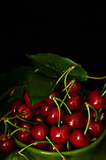 Fresh ripe cherries with green leaves on black background.