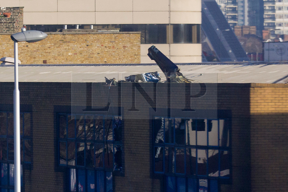 © Licensed to London News Pictures. 17/01/2013. London, UK. Helicopter parts are seen on the roof of a building near Vauxhall after a helicopter hit a crane attached to the St George's Wharf development in Vauxhall, London, yesterday (17/01/13). 2 (two) people, including the pilot, died as a result of the incident and a further 11 (eleven) injured after the Augusta 109 helicopter collided with the crane in heavy mist showering wreckage onto cars below. Photo credit: Matt Cetti-Roberts/LNP