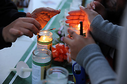 "Participants light ""luminarias"" in preparation for the candlelight procession. In a touching final celebration of All Soul's Day on Saturday night, hundreds of congregants came to Queen of Heaven Cemetery in Salinas to attend mass, and offer their prayers. Friends and family members sat by the graves of loved ones, many of which were decorated with traditional Day of the Dead marigolds, photographs of the departed, and things that were their favorites in life."