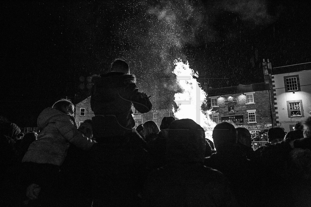 Allendale Town, New Year's Eve 2017. Men are carrying burning barrels filled with tar, sawdust, kindling and paraffin on their heads.<br /> The Tar Barl Festival has been Allendale's way of welcoming the new year for at least 160 years.<br /> The normally quiet village heaves with people - locals, visitors and the barrel-carrying &quot;guisers&quot; wearing fancy dress or a disguise. <br /> A fiery procession swarms round the Northumberland village, returning to the square just before midnight to throw its barrels on to the waiting bonfire, setting it alight.