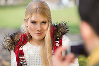Beautiful young woman being photographed by man in park