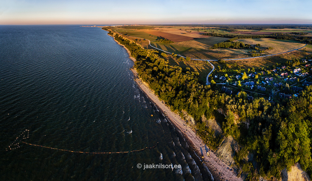Estonia, Baltic sea coast near Päite village. Aerial view, sunset. Steep bank, road, village.