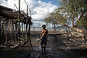 A young Moken fisherman takes a break after repairing boats in Koh Lao Moken village, Ranong province, southern Thailand.