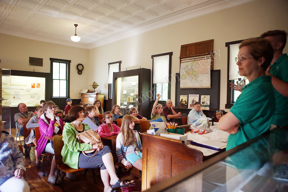 Grandparents and grandchildren listen to a presentation in the One-Room Schoolhouse as part of Grandparents U photo Emily Mesner
