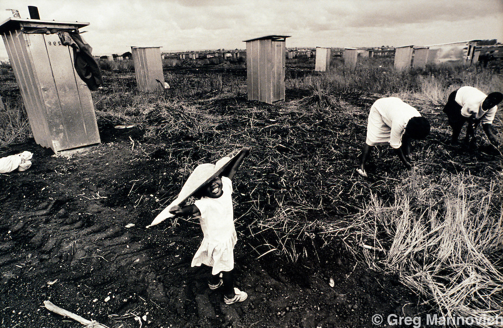 Diepsloot, Soweto, Johannesburg, Transvaal, South Africa, 1991: A girl plays as women clear the land next to toilets where they can erect shacks on open land earmarked for more informal development.