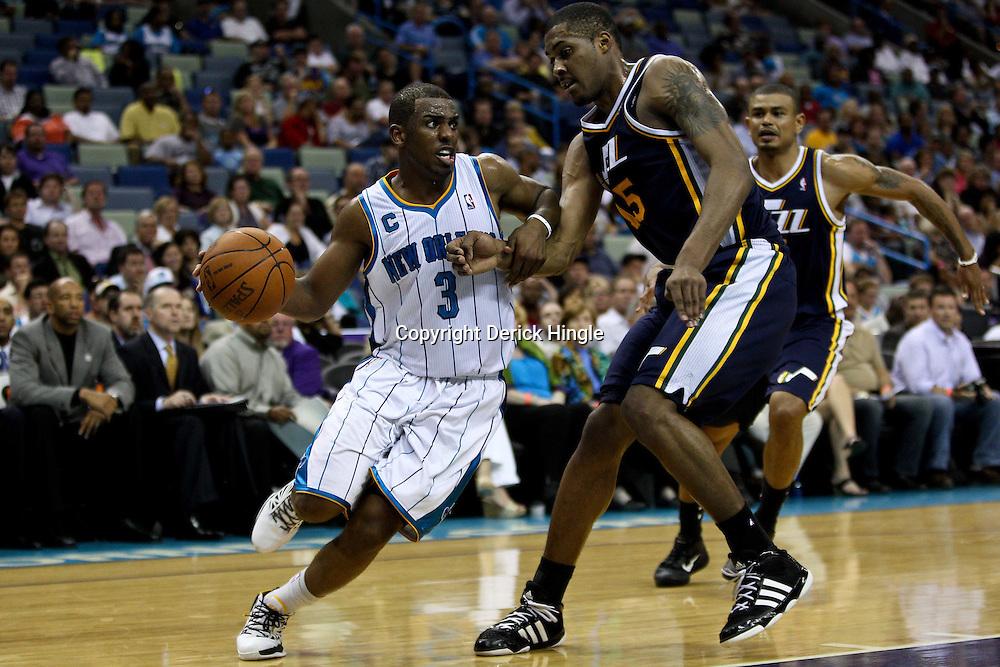 April 11, 2011; New Orleans, LA, USA; New Orleans Hornets point guard Chris Paul (3) drives past Utah Jazz power forward Derrick Favors (15) during the second half at the New Orleans Arena. The Jazz defeated the Hornets 90-78.  Mandatory Credit: Derick E. Hingle