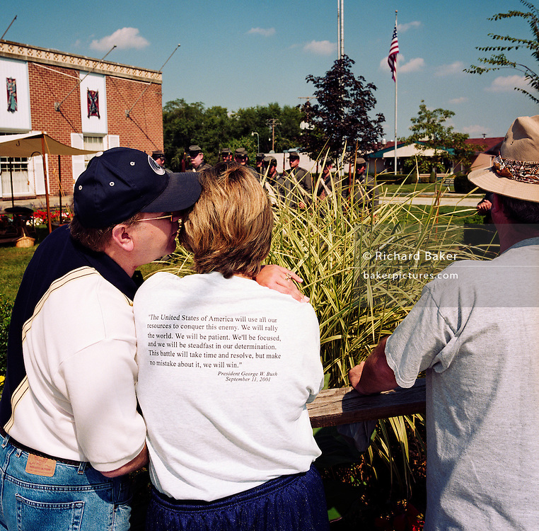 During a journey into America's hinterlands, days after the September 11th attacks in New York and Washington DC, we see visitors watching a re-enactment of a Civil War skirmish at the Gettysburg National Military Park. As a group of Confederate troopers parade on the battlefield, we see printed on a woman tourist's back, the quoted words spoken by President George W Bush on 9/11/01. His rallying call to the nation, answering the demand for vengeance against the 'evil-doers' is included in his rhetoric, reproduced on clothing and on messages displayed around the US. The American Civil War's Battle of Gettysburg was fought in and around the town of Gettysburg, Pennsylvania and was the one battle with the largest number of casualties: Between 46,000 and 51,000 killed in the three-days in July 1863.