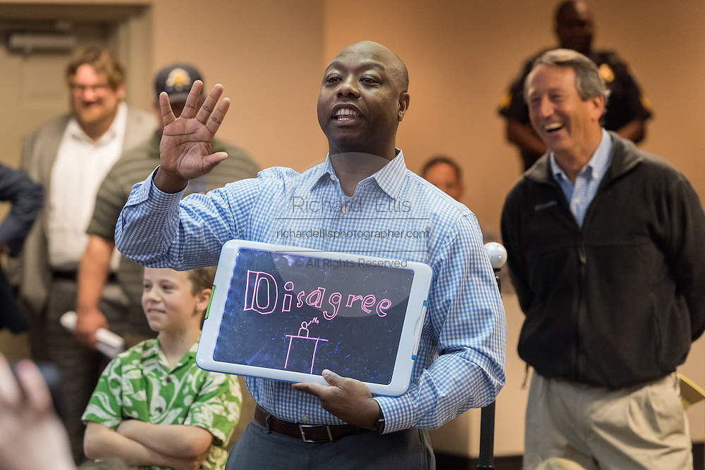 U.S. Sen. Tim Scott holds up a protestors sign during a light moment in a heated debate with angry constituents at a town hall meeting February 18, 2017 in Mount Pleasant, South Carolina. Hundreds of concerned residents turned up for the meeting to address their opposition to President Donald Trump during a vocal meeting held by U.S. Rep. Mark Sanford and Senator Scott.