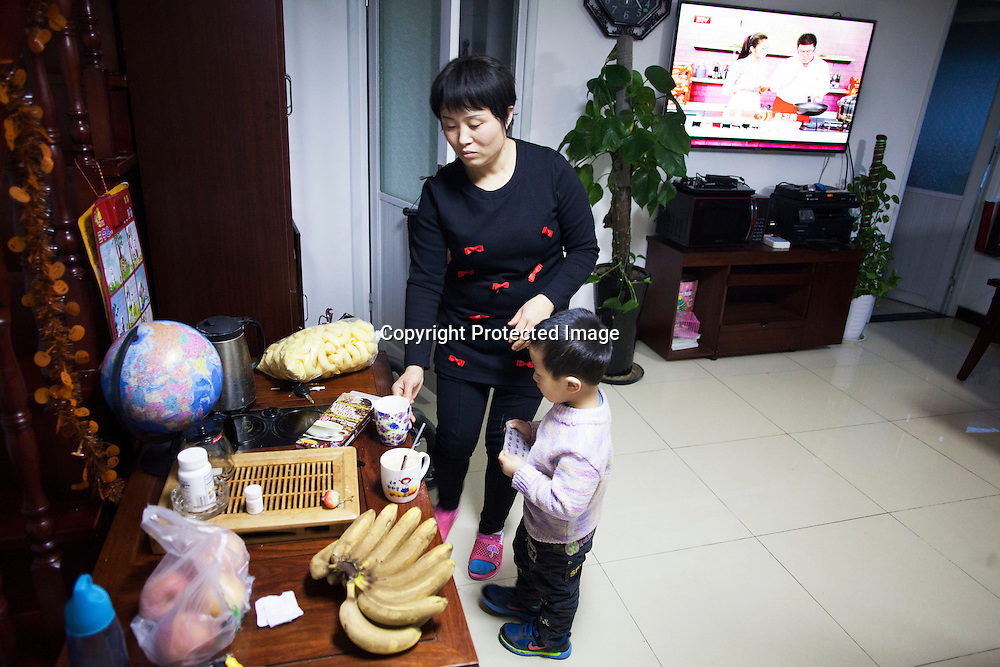 Beijing, March 11 : Cui Xinying helps her youngest son, Tian Ye in the kitchen while her eldest son, Tian Peng, 15, lies in the sofa.<br />